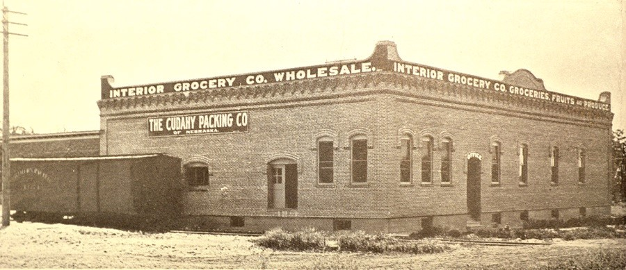 The Interior Grocery Company ca. 1910 showing the north façade on the right and the east façade with a Northern Pacific box car on the rail spur. Photo from Walla Walla: The Garden City, n.d. Courtesy Northwest & Whitman Archives.