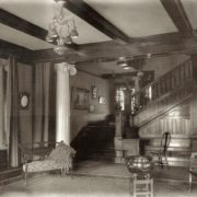 The entrance hall staircase, demolished, is now a pool room. Whitman Archives photo.