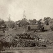 "Looking north across the ""sunken garden"" ca. 1910. The two Langdon boys can be seen, one of them perched on the moss rock bridge over Butcher Creek. Whitman Archives photo."