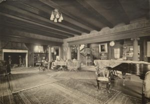 The grand living room with inglenook fireplace, left; entrance hall and staircase, right center; dining room, far right. Whitman Archives photo.